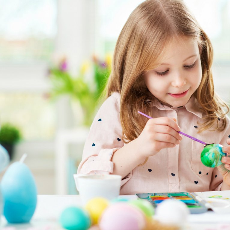 Young girl painting egg